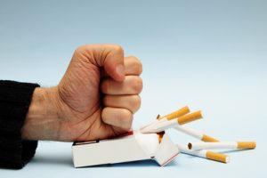 man hand crushing a packet of cigarettes, stop smoking concept